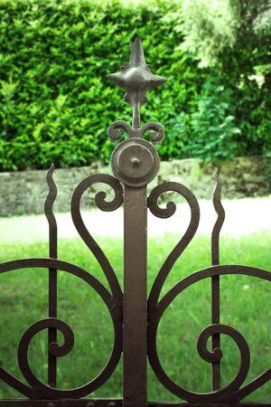 puertas de hierro: Detalle de una puerta de la vendimia con césped y seto en el fondo