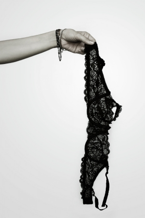 hand bra: Detail of a female arm holding up a black lace bram on light grey background