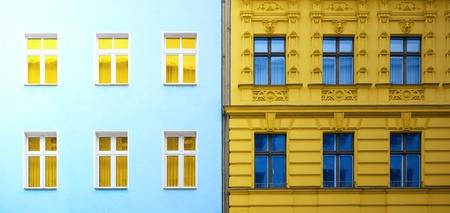 old building facade: Two facade of different buildings with yellow and blue colors inverted Stock Photo
