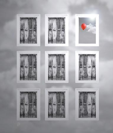 Fantasy rolluiken in een bewolkte muur en een venster dat wordt geopend en het wolkje met rode ballon in zwart-wit Stockfoto