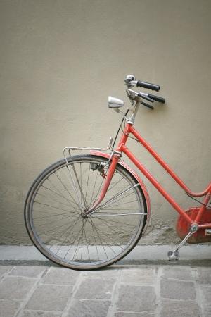 Detail van een rode vintage fiets leunend tegen een muur