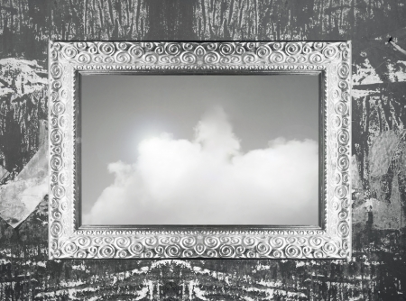 Elegant silver frame hanging on wall with an imagine of sky and clous in black and white