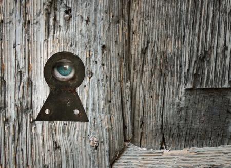 Human eye looking through an old keyhole photo