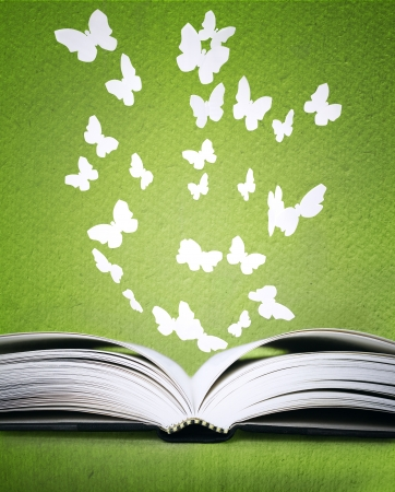 An opened book with stylized butterflies above on a green background texture