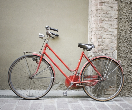 Beautiful old red bicycle leaning on an wall
