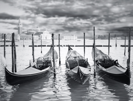Wonderful view of three gondola parking in Grand Canal with the island with -Basilica of Virgin Mary of Good Health- and dramatic sky on the background in black and white photo