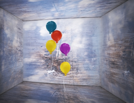 Fantasy box inside with sky and clouds on the walls and wooden texture with five colorful balloons that flying inside of it photo