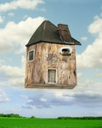 Fantasy background of an inventive-collage house that flying with lawn and sky with clouds on the background