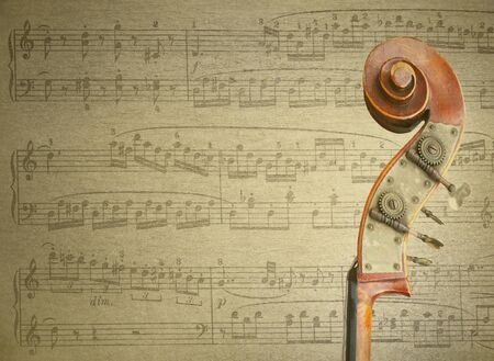 musical score: Detail of an handle of a cello with musical score on the background Stock Photo