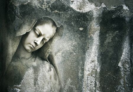 Background of an grungy dark wall with a beautiful detail face of a sculpture of a female saint