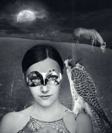 彼女の肩に白と黒の芸術の背景にホークとマスクの若い女性の神秘的なファンタジー背景 写真素材