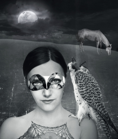 Mysterieuze fantasie achtergrond van een jonge vrouw in masker met een havik op haar schouder in een artistieke achtergrond in zwart en wit