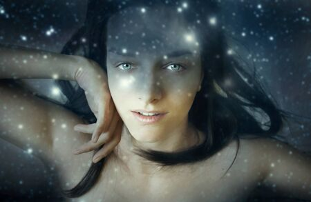 mystery woman: Portrait of a beautiful young woman in a fantasy night sky with stars background Stock Photo