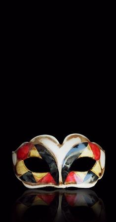 arlecchino: Bella maschera di Arlecchino con la sua riflessione sopra isolato su sfondo nero Archivio Fotografico