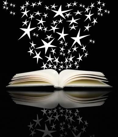An open book with many bright stars on black background and its reflection above photo