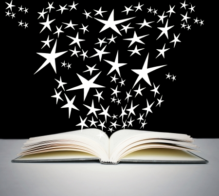 An open book on a grey table with many bright stars on black background