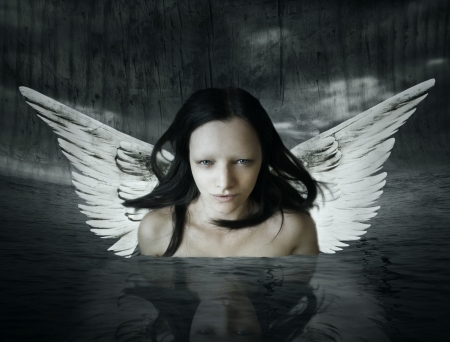 Angelic being that comes out of the water in a setting dark background Stock Photo