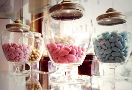 Veel glazen containers met verschillende kleuren van gesuikerde amandel