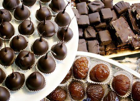 glace: Detail of many maraschino cherries covered in dark chocolate, marron glace and dark chocolate nougat