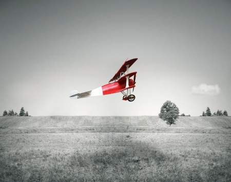 Fantasy flight of an old red airplane flying on a field and sky in black and white Stock Photo