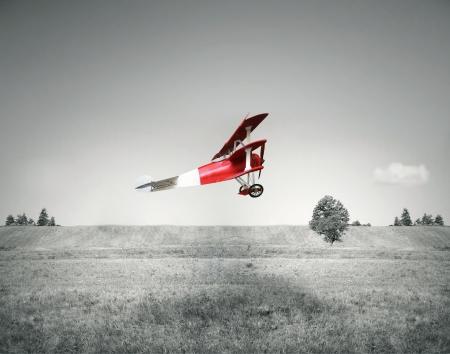 juguetes antiguos: Vuelo de la fantasía de un avión viejo rojo volando en un campo y el cielo en blanco y negro Foto de archivo