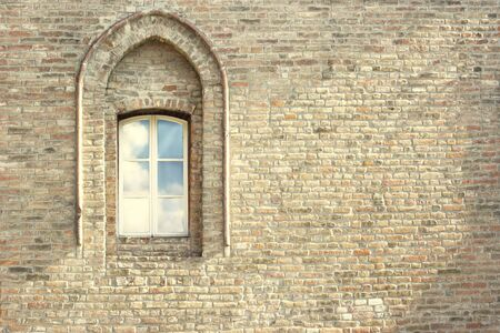 Detail of an ancient brick wall with an arched window  photo