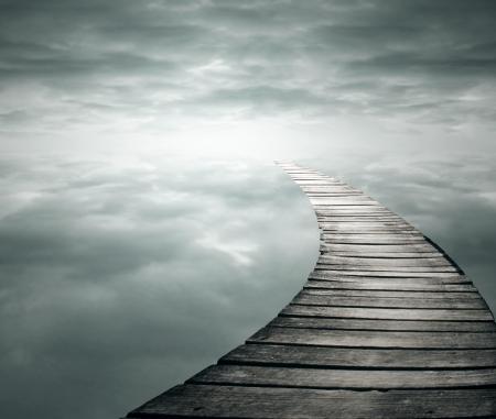 Mooie poëtische achtergrond met een houten loopbrug in de oneindigheid hemel Stockfoto