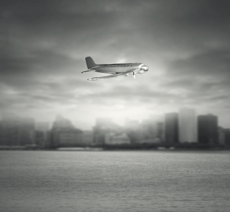 Artistic composition of a vintage airplane toy in flight under the sea with a city and dramatic sky in the background in black an white photo