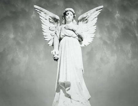 angel statue: Beautiful full length of an angel with a cloudy sky on the background in black and white Stock Photo