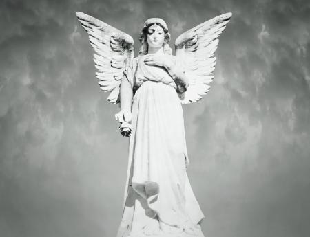 Mooie volle lengte van een engel met een bewolkte hemel op de achtergrond in zwart en wit