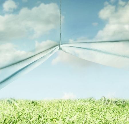 生地で作られた空を表す芸術の超現実的な背景、フックと牧草地の草と空の上でプルアップ 写真素材