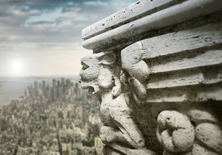 ledge: Beautiful sculpture on the ledge of a building with panoramic modern cityscape and sky  on the background Stock Photo