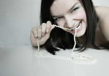 Funny portrait of a beautiful elegant girl that biting a pearl necklace photo