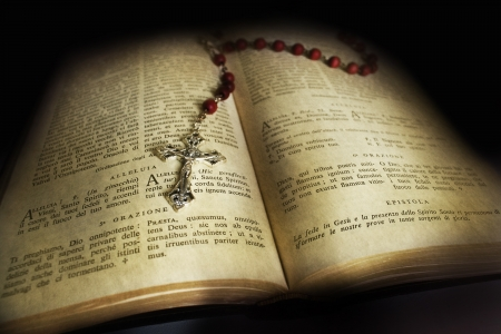 christmas prayer: An old open Holy Bible with a red rosary on top Stock Photo
