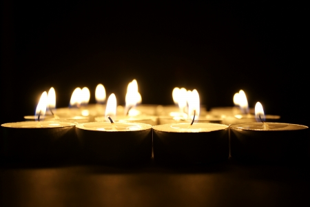 Many religious lighted candles in the darkness