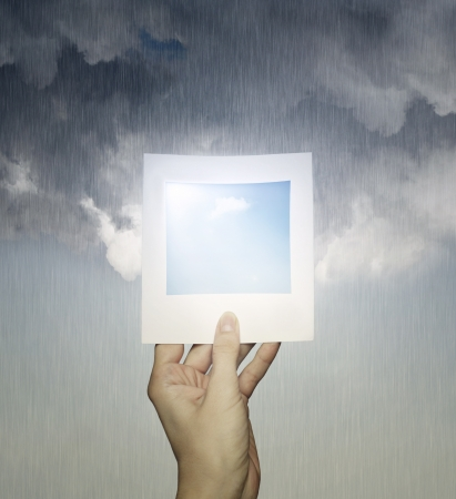 raining background: Conceptual imagine of a hand holding a picture with a clear sky and a cloudy sky with rain in the background
