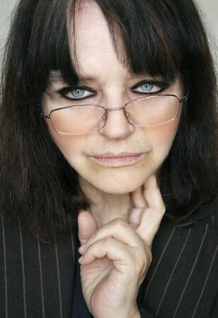 beautiful middle aged woman: Beautiful middle aged woman portrait with eye glasses with a concentrated expression
