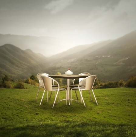 A modern table and four chairs outdoor on the grass with a wonderful mountains panoramic view at sunset