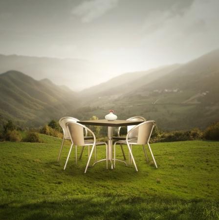 Een moderne tafel en vier stoelen buiten op het gras met een prachtig panoramisch uitzicht op de bergen bij zonsondergang Stockfoto
