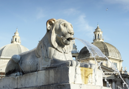 Detail of a beautiful lion fountain with two domes and blue sky in the background in Rome photo