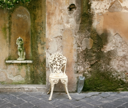 unique characteristics: A characteristic and decadent corner of an old crumbling wall with an old wrought iron chair and a little statue Stock Photo