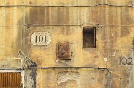 decadence: Detail of a old and decaying wall with the number 101 and 102 and wires light