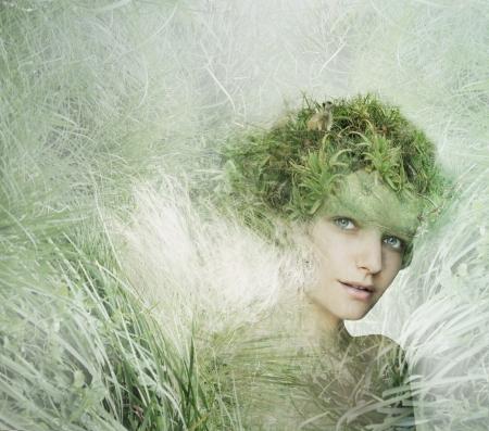 自然の一部で、功妙な想像力豊かなドレスを持つ若い女性モデル
