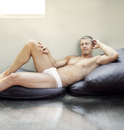 Handsome young male model lying in undewear on pillows photo