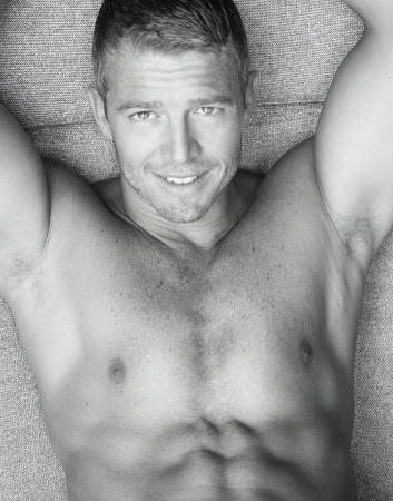 abdomen fitness: Portrai de un apuesto modelo sonriente hombre conf�a en blanco y negro