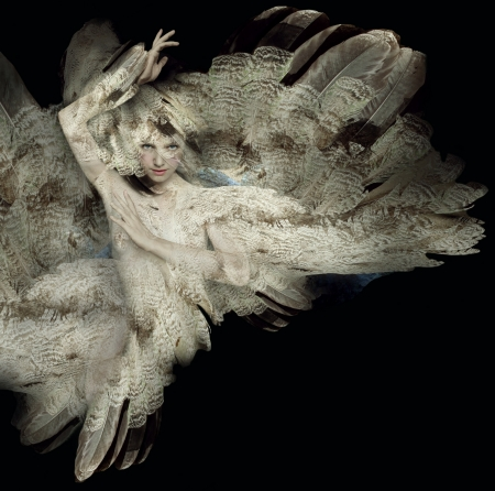 Beautiful artistic portrait of a girl with plumage on black background