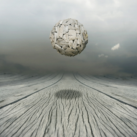 Artistic metaphysical background representing a ball sculpture floating in the air above a wooden floor with the sky on the background photo