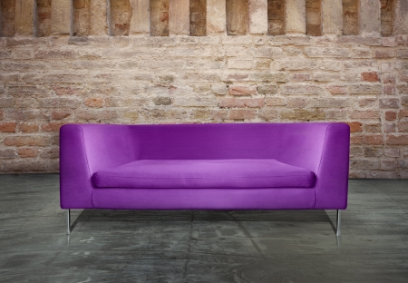 Minimalist modern purple sofa in a unusual environment antique brick wall photo