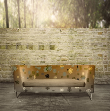 Modern golden sofa in a unusual environment with an antique brick wall and plants photo