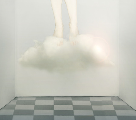 Artistic surreal conceptual image that represent two human legs and feet under a cloud that fly away from a claustrophobic room photo
